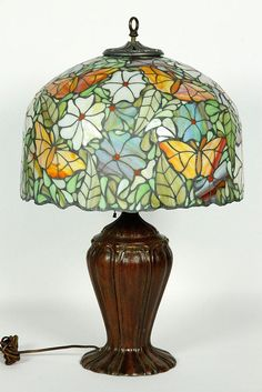"""Attributed to Handel lamp, bronze base with leaded glass shade with flowers and butterflies, 27""""h (base), 10 1/2""""h x 17 1/2""""dia (shade). Provenance: Newton, MA estate."""