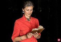 Sahra Wagenknecht in rotem Klein mit Buch in der Hand