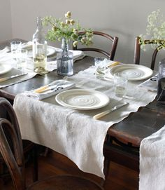 A motley assortment of vintage bentwood chairs surrounds an 18th-century oak table in this Rhode Island home's dining room. The linen runners are from a Vermont antiques shop.