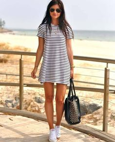Черно-белое платье в полосочку, золотистые часы, браслет и подвеска, черная сумка, черные очки, белые кеды.