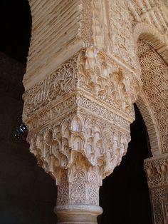 Alhambra Palace in Granada, Spain - Muqarnas plasterwork and Islamic writing on a column.