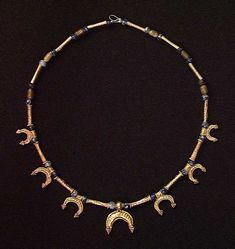 A LATE ROMAN GOLD NECKLACE, ca. 4th century AD. Consisting of tubular gold beads interspersed with blue glass beads and with 7 gold crescent pendants with granulation. 14.5 inches.