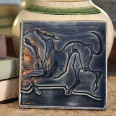 Featuring my leaping Greyhound Whippet design incised into the tiles surface. It measures approximately 4 x 4 x 5/16 (size varies slightly due to its handmade nature). Notched in the back for hanging.This tile is handmade of earthenware clay by me, Sarah Regan Snavely, in my North Dakota studio. Artist signed.