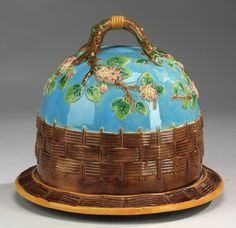 English majolica cheese dome and underplate attributed to George Jones, having a double twig form handle surmounting a turquoise glazed dome with bas relief trailing dogwood branches above a band of brown basket weave, resting on a conforming basket weave tray, with a cream interior and a mottled green and brown underside, unmarked.