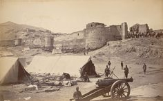 Photograph John Burke 1879, 2nd Afghan War (1878-80), with a view of the damaged Bala Hissar fortress at Kabul in Afghanistan showing soldiers posed in the foreground and camels being led into the fort in the background