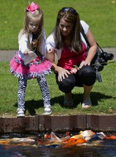 Four-year-old Grayson Gist feeds the fish with her mother Nicole at the Koi pond at the Japanese Garden before attending the annual Mother's Day Brunch at the Memphis Botanical Gardens on Sunday. (Chris Desmond/Special to The Commercial Appeal)