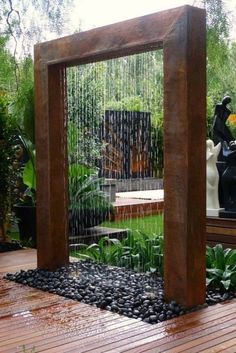 Outdoor rusted metal and pebble water feature.