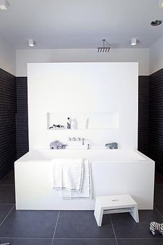 The low wall divides the bathroom in separate area's, giving the one soaking in the tub a bit of extra privacy