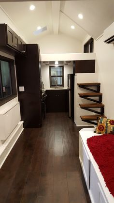 Cornerstone Tiny Homes, Florida, 28 foot, tiny house on wheels, THOW The Fontana. 2 loft, 2 staircase, walk thru shower with slate tiles, sink built over trailer tongue, espresso cabinets, stainless steel fridge, stainless steel sink, can lighting, espresso tile flooring, sunken bed, back-lit wine rack, tall pantry, tile backsplash, floating stairs, cubby for washer and dryer combo in bathroom