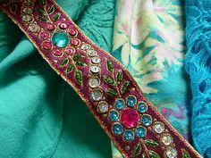 Ein faszinierendes Web Band.   Das Web Band hat die Grundfarbe dunkel pink.   Die Grundfarbe von dem Web Band glitzert leicht.   Die Farben von dem Webband sind dunkel pink, grün, türkis,silber und gold.   Auf dem Webband befindet sich ein üppiges Muster bestehend aus Perlen und Stickerei.   Die Perlen sind alle aufgenäht und nicht geklebt.   Die Blumen und Blätter die sich auf dem Webband befinden bestehen aus plastischen Ornamenten die sich leicht über das Webband erheben.
