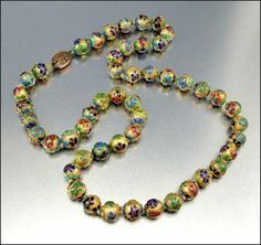 Smashing and colorful vintage Chinese enamel and gold dore bead necklace from the early 1940s! Long, heavy and fabulous metal beads have a gold dore base with raised enamel flowers in red rust, cobalt blue, turquoise, emerald and lime green. Hand knotted between each bead with a pale cream silk, the necklace closes with a filigree clasp. Very striking!