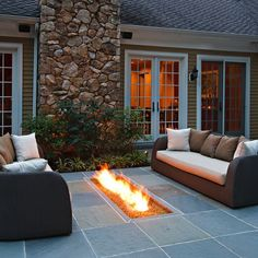 An in-ground fire pit lights and warms up this patio sitting area. A pair of wicker sofas flank the fire pit, offering a convenient spot for chatting with family and friends.