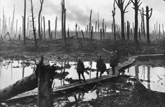 Soldiers of an Australian 4th Division field artillery brigade walk on a duckboard track laid across a muddy, shattered battlefield in Chateau Wood, near Hooge, Belgium, on October 29, 1917. This was during the Battle of Passchendaele, fought by British forces and their allies against Germany for control of territory near Ypres, Belgium. (James Francis Hurley/State Library of New South Wales)