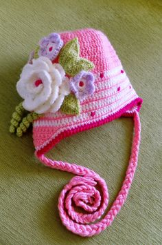 Warm crocheted children hat in pink with a beautiful flowers