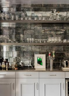 Gray contemporary wet bar features light gray cabinets accented with polished nickel pulls and a gray quartz countertop fitted with a beer tap and a square sink with modern chrome faucet fixed beneath gray floating shelves mounted on antiqued mirrored subway backsplash tiles.