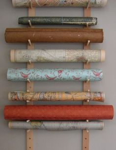 """Wrapping paper storage. My thought is to put a dab of hot glue on the """"up"""" side of each dowel (and make sure they're always glue-side up, if rearranged) to make a kind of bumper, or drill the holes at a slight angle so the dowels tilt up just enough to keep the rolls from rolling off."""