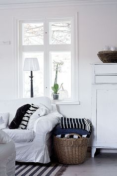 STAGING :: I love the use of baskets filled w/ blankets & throws next to couches in place of end tables.