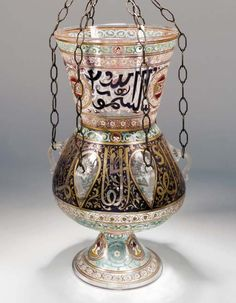 A MAMLUK STYLE ENAMELLED AND GILDED GLASS MOSQUE LAMP  Europe or North Africa, After the Imberton copy of the Mamluk original, with typical rounded body on spreading trumpet foot and with flaring conical mouth, the body with six applied loop handles dividing a band of Mamluk thuluth on blue ground, the mouth with a band of similar gold-outlined blue inscription on clear ground with white scrolling vine interrupted by three blazon roundels, underside of the body with turquoise scrolling…