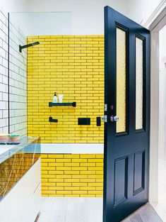 bright yellow subway tile and black hardware and black door in the bathroom