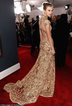 Taylor Swift arriving at the Grammy awards wearing a stunning glittering cheongsam-inspired golden gown featuring a high neck cut and caplet sleeves