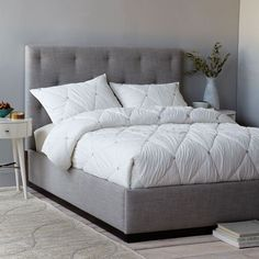 The Diamond Tufted Bed mixes staggered tufting and an exposed wood base with crisp upholstery in Platinum, for an elegant, put-together look.