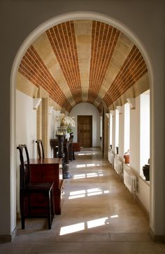 Barrel vault ceiling hallway - brick alternated with concrete to creates stripes that carry your eye down the length - your eye immediately goes to door...beautiful detail!