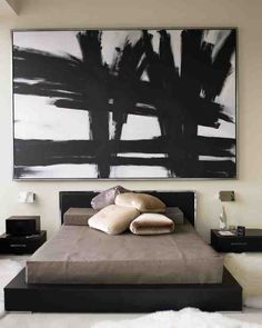 """I wanted the bed to look like a bento box,"" Kevin Sharkey, the owner of this city apartment said. A can't-go-any-lower black-stained bed and marble-topped side tables achieve the effect. An oversize graphic painting keeps the furniture grounded in the soaring room."