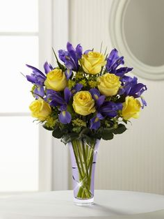 Sunlit yellow roses are arranged with deep purple iris and lush greens, presented in a lavender designer glass vase via frugal flower