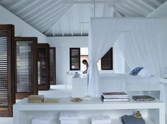 Beach House by Adam Design - wall of shutter doors contrasting with white room.