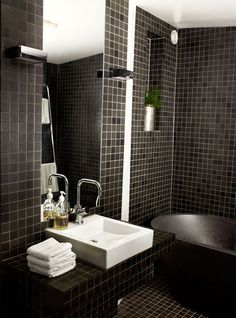 Your first impulse for a tiny bathroom might be lots of optic white. Instead, play up the close quarters with a darker hue. Black tiles and fittings lend this Stockholm attic bathroom a dramatic look. The black bathtub is made of recycled plastic, and the Mora faucet was initially intended for use in a kitchen, though it allows more room here in tight quarters. Photo by Per Magnus Persson.  Courtesy of: Copyright Per Magnus Persson