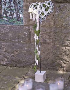 Floristisch gestaltete Formen auf einem Stab, entweder zum Einstecken oder wie hier auf beschwerendem Steinfuß