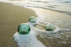 Green glass fishing floats washed up on a beach at sunset