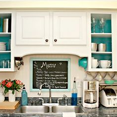Open kitchen cabinets painted aqua on the inside with aqua, green, white, and silver accents.