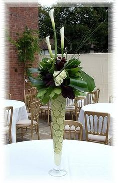 I like the idea of limes or artichokes in a tall vase with a lot of green and white at the top.  I'd replace the dark flower with more white.
