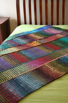 "64 Crayons by Amy Swenson -- basically the two-row ""brooklyn tweed scarf"" with strips sewn together to make a blanket. Each strip uses two contrasting colorways of Kureyon (did you know that's Japanese for crayon??)"