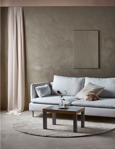 A modern sofa in a minimalist living room with a single piece of art on the wall and a simple sofa table