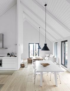 Beautiful white dining area. Natural floor boards. Touch of black
