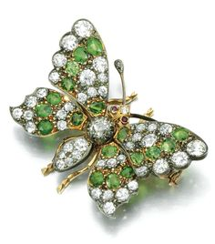 Demantoid garnet and diamond brooch, late 19th century. Designed as a butterfly its wings set en tremblant with circular cut demantoid garnets, cushion shaped and circular cut diamonds, the eyes set with circular cut rubies