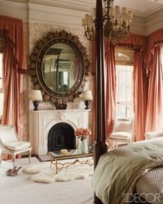 coral and cream bedroom in a New Orleans mansion; gilded-iron cocktail table, 19th century Italian chairs, antique giltwood mirror, and dramatic curtains