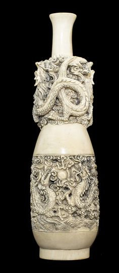 CHINESE CARVED IVORY VASESigned, of elongated ovoid form, with a central band on the body and neck, carved with dragons in pursuit of a sea pearl. Height 9 ½ in. Weight 735.3 g.