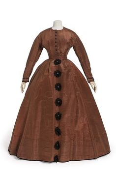 Ca.1865 brown silk moire dress. Maroon satin buttons trimmed with black lace. Les Arts Decoratifs.
