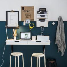 Un porte-revue au-dessus du bureau. Ici, le manque de rangements n'est pas un problème, les porte-revues prennent de la hauteur et viennent se fixer sur le mur. La couleur vert canard au mur apporte une sensation de profondeur à l'espace de travail et le blanc du bureau apporte de la clarté pour une ambiance un brin épurée idéale pour travailler avec sérénité.