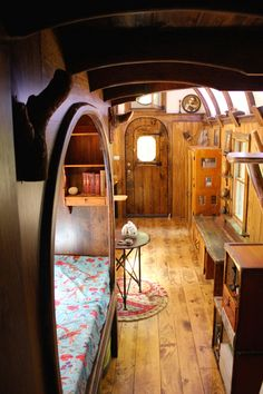 A sleeping nook with a curved opening is part of the detailed woodwork found in the Old Time Caravan. A one-of-a-kind tiny house with a curved roof, round windows, live edge maple desk, mahogany storage staircase, and intricate woodwork throughout. Best Tiny House, Tiny House Plans, Tiny House On Wheels, Inside Tiny Houses, Tiny House Living, Small Living, Bus Living, Living Room, Tiny House Bedroom
