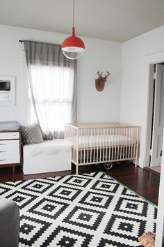A pop of color from the light fixture, with a very graphic black and white rug.  Antlers is an interesting choice for a baby's room!  Is Dad a hunter?