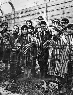 Children behind a barbed wire fence at the Nazi concentration camp at Auschwitz, in southern Poland, where the role of former workers is still the subject of a probe by prosecutors investigating war crimes.