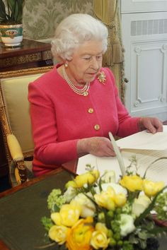 Queen Elizabeth II delivered her Commonwealth Day message at Buckingham Palace wearing a pink jacket teamed with pearl jewelry, March 11, 2013.