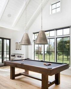 Stunning games room boasts tongue and groove clad vaulted ceilings adorned with a pair of Goodman Hanging Lamps over a Pottery Barn Pool Table surrounded by steel framed windows and a stainless steel floating shelf which doubles as a bar paired with industrial barstools atop white oak floors.