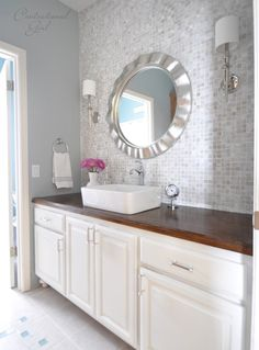 bathroom vanity wall makeover. Easy to recreate? Say with lowes stock cabinets, furniture feet, stained butcher block counters and vessel sink? hmm...