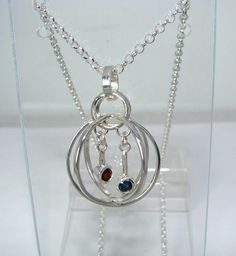 Cage pendant in sterling silver with blue sapphire and red garnet