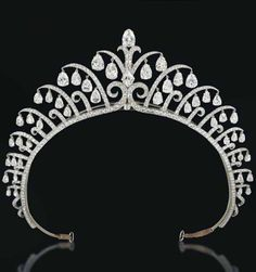 AN ART DECO DIAMOND TIARA, BY CARTIER. Designed as a series of graduated diamond-set scrolls, each suspending pear-shaped diamond flexible pendants, centering upon a lozenge-shaped diamond, 1920s, inner diameter 12.0 cm, in red leather fitted Cartier case. Signed Cartier London